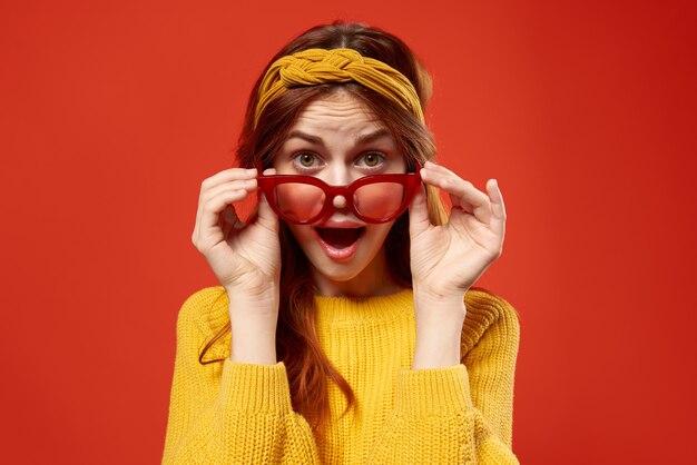 赤い眼鏡のヘッドバンドヒップスターファッションポーズのきれいな女性