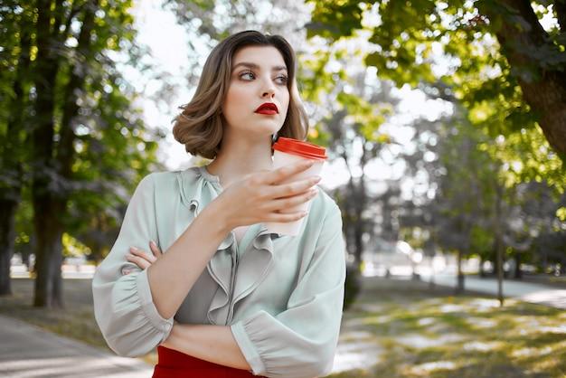 赤いスカートをはいたきれいな女性が公園でコーヒーを飲みながら散歩レジャー
