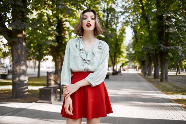 公園の散歩ライフスタイル新鮮な空気の赤いスカートのきれいな女性