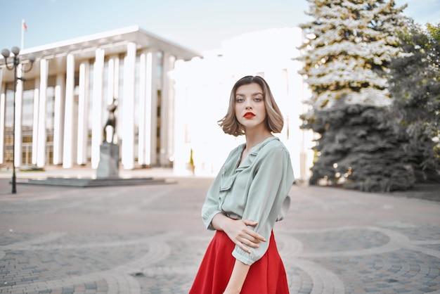 屋外の街を歩く赤いスカートのきれいな女性