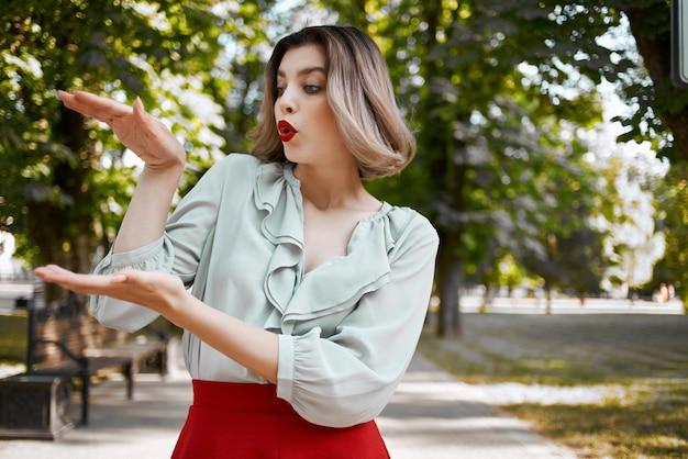 公園の木々の新鮮な空気のポーズを歩いて赤いスカートのきれいな女性