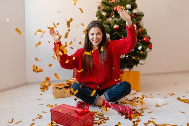 Красивая женщина в красном свитере сидит дома у елки, бросая золотое конфетти в окружении подарков и подарочных коробок