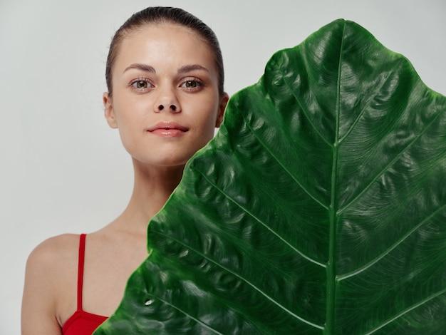 ヤシの葉の後ろに隠れている赤い水着のきれいな女性