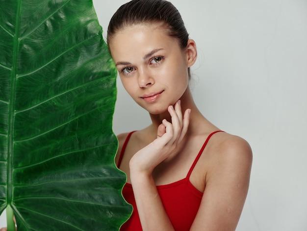 赤い水着のきれいな女性ヤシの葉の手のジェスチャーの魅力