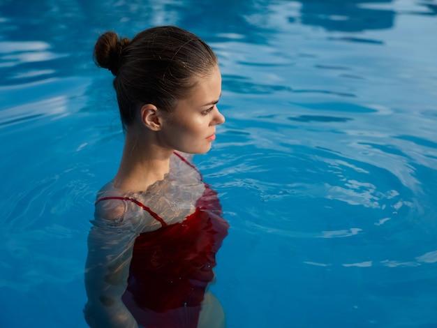 赤い水着のプールの贅沢な休暇のきれいな女性