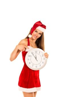 白い背景の上に時計を示すサンタ クロースの衣装できれいな女性