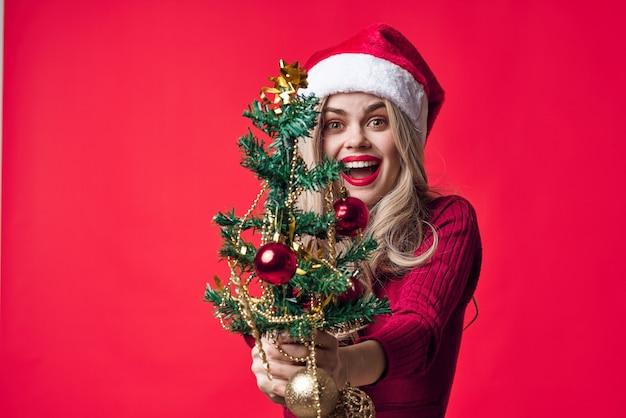 手にクリスマスツリーとサンタクロースの衣装を着たきれいな女性伝統休日分離
