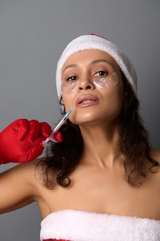 サンタの衣装を着たきれいな女性と目の下の滑らかなパッチは、美容注射器で注射器を保持しています。スキンケアの若返り、アンチエイジングケア。クリスマスプレゼントのための美容スパサロンのためのスタジオショット