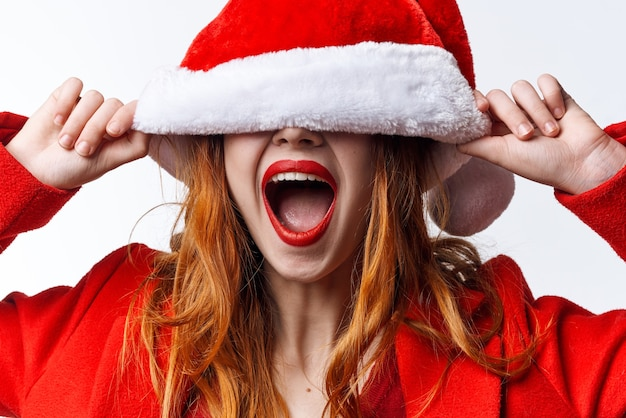 サンタ帽子の休日のクリスマスの楽しい感情のきれいな女性