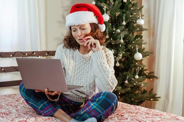 Красивая женщина в шляпе санты делает трудный выбор при покупке подарков в интернете на рождество