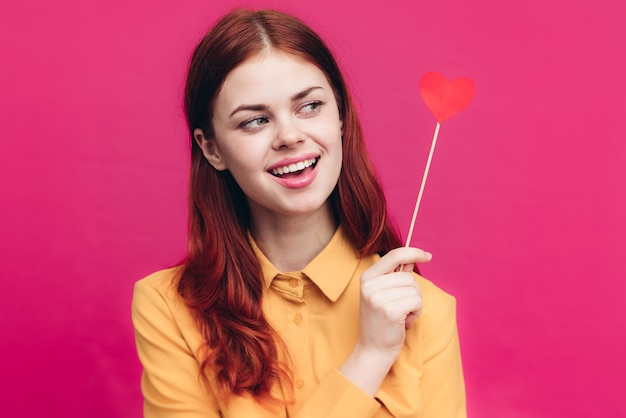 ピンクの背景にスティックにハートを保持しているシャツのきれいな女性