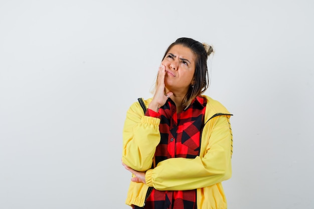 シャツを着たきれいな女性、頬に手をつないでいるジャケット、見上げて物思いにふける、正面図。