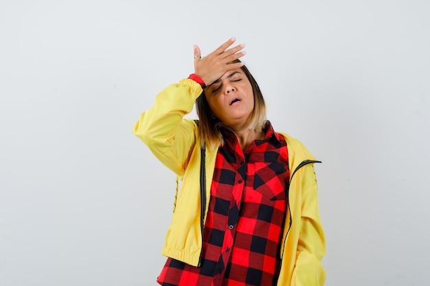 シャツを着たきれいな女性、額に手を置いて忘れて見えるジャケット、正面図。