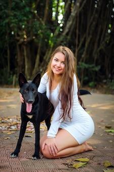 Красивая женщина в коротком платье и черная собака, играя на открытом воздухе