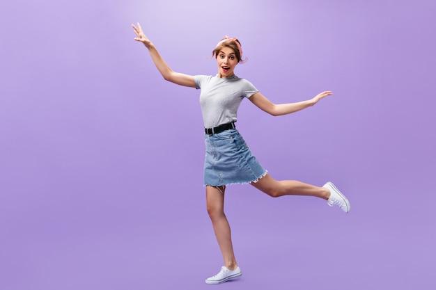 スカートとシャツのきれいな女性が紫色の背景にジャンプします。白いスニーカーのポーズでスタイリッシュな髪型を持つ面白い若い女の子。