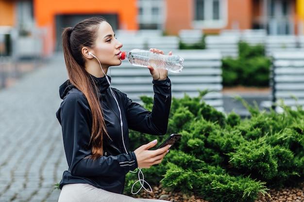 운동복을 입은 예쁜 여자, 아침 달리기 후 신선한 공기를 마시는 물. 건강한 개념입니다.