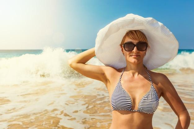 ビーチでストライプのビキニ、サングラス、白い帽子のきれいな女性、
