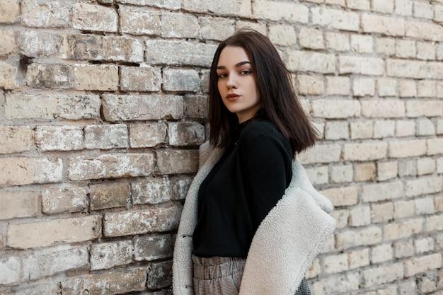 Красивая женщина в стильной одежде с курткой позирует возле кирпичной стены