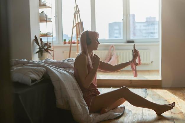 바닥에 큰 침대 근처에서 셀카를 찍는 헤드폰을 끼고 세련된 잠옷을 입은 예쁜 여자