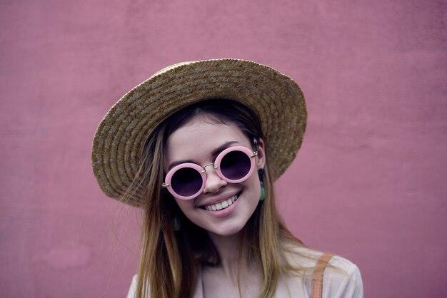 예쁜 여자 선글라스와 모자 미소 매력적인 모습 분홍색 배경.