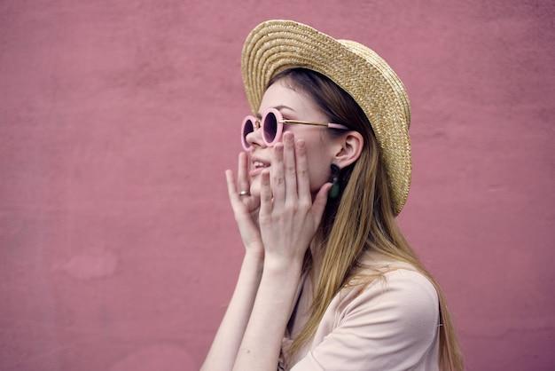 선글라스 패션 모자 도보 분홍색 벽에 예쁜 여자