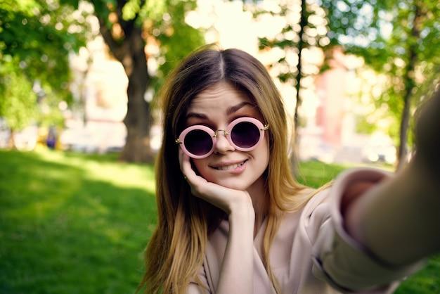公園の夏のライフスタイルでサングラスをかけたきれいな女性。高品質の写真