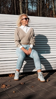 Красивая женщина в солнцезащитных очках на скамейке в осеннем парке только, концепция людей образа жизни