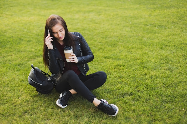 サングラスのきれいな女性は都市公園の芝生でリラックスし、スマートフォンで友達と話し、ブラックコーヒーを飲む