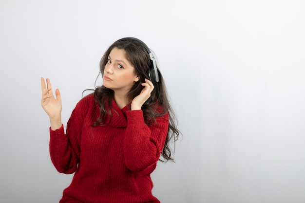 お気に入りの曲を聴きながらワイヤレスイヤホンで音楽を楽しむセーターのきれいな女性。