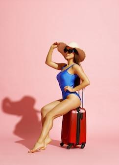 Красивая женщина в купальнике и шляпе позирует с чемоданом на розовом