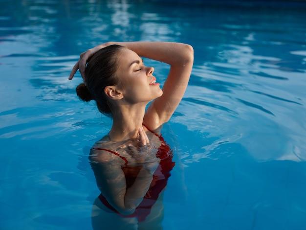 水着姿のきれいな女性がプールの贅沢な目を閉じた自然を見つめます。高品質の写真