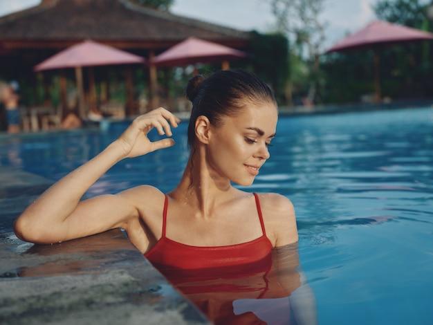 プールの自然ホテルの休暇で水着姿のきれいな女性。高品質の写真