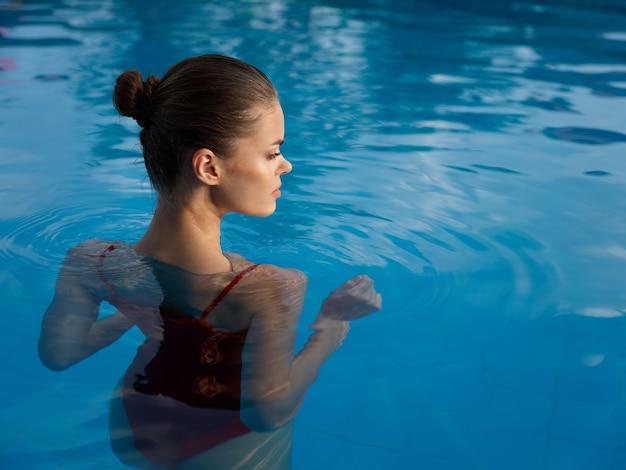 水着姿のきれいな女性が透明な水の背面図でプールのタイルの上に立っています