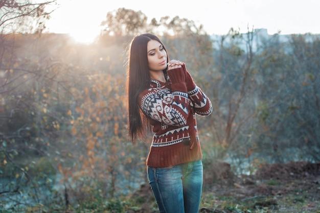 Красивая женщина осенью перед закатом