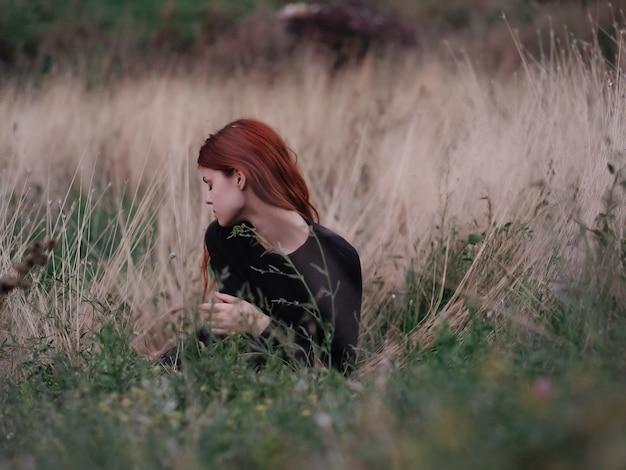 フィールドのきれいな女性は草の夏のロマンスに横たわっています