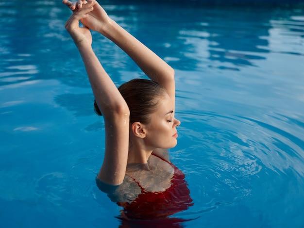 プールのきれいな女性は彼女の頭の上に彼女の手を保持します