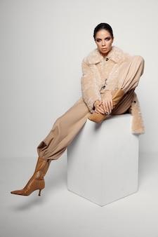 トレンディな秋の服の明るい化粧コートのきれいな女性