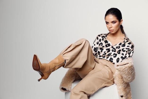Красивая женщина в модной осенней одежде леопардовой рубашки студии