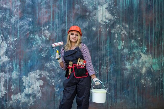 制服を着たきれいな女性と家を改築する準備をしているペイントとローラーを保持しているヘルメット。建設労働者。