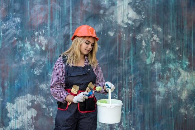 制服を着たきれいな女性と家を改築する準備をしているペイントとローラーを保持しているヘルメット