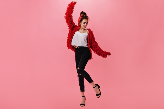 Красивая женщина в теплой куртке и джинсах танцует на розовом