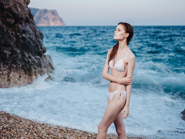白いビキニのビーチの岩のきれいな女性