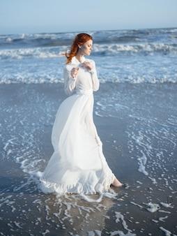 海のポーズの休暇で白いドレスを着たきれいな女性
