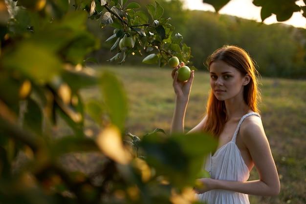 リンゴの木の近くの白いドレスフィールドのきれいな女性
