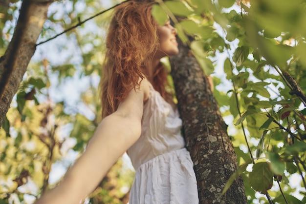 木の底面図の白いドレス自然緑の葉のきれいな女性。高品質の写真