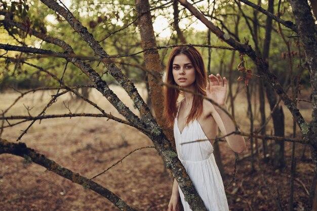 Красивая женщина в белом платье возле деревьев опавшие листья в лесу