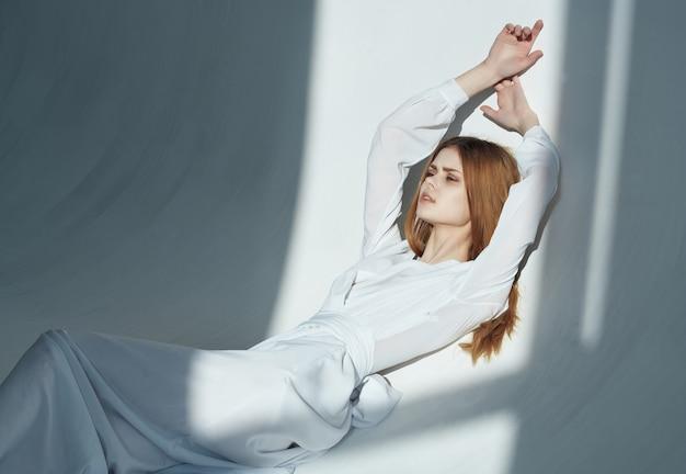 魅力的な明るい背景のポーズをとる白いドレスのきれいな女性。高品質の写真