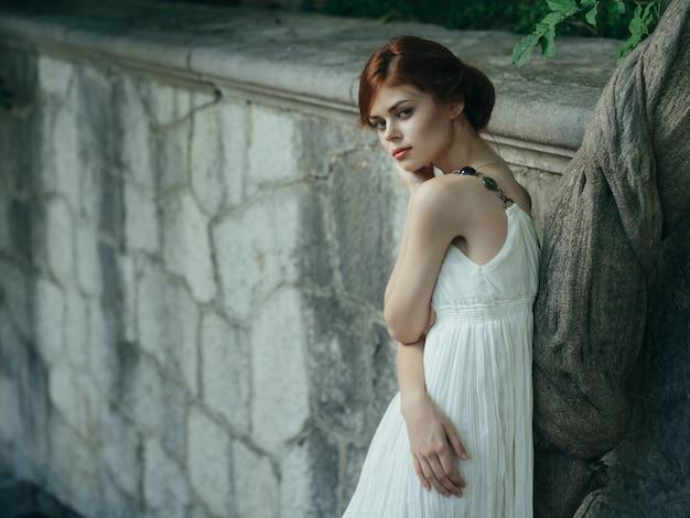 그리스 나무 근처 자연에서 포즈를 취하는 흰 드레스를 입은 예쁜 여자
