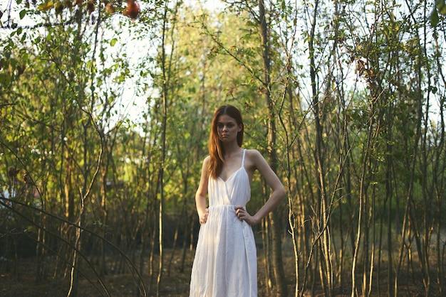 白いドレスを着たきれいな女性が森の中を歩く自然休息
