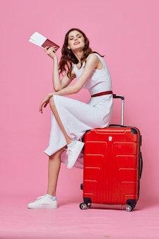 Красивая женщина в белом платье в шляпе красный чемодан паспорта билеты на самолет розовый фон